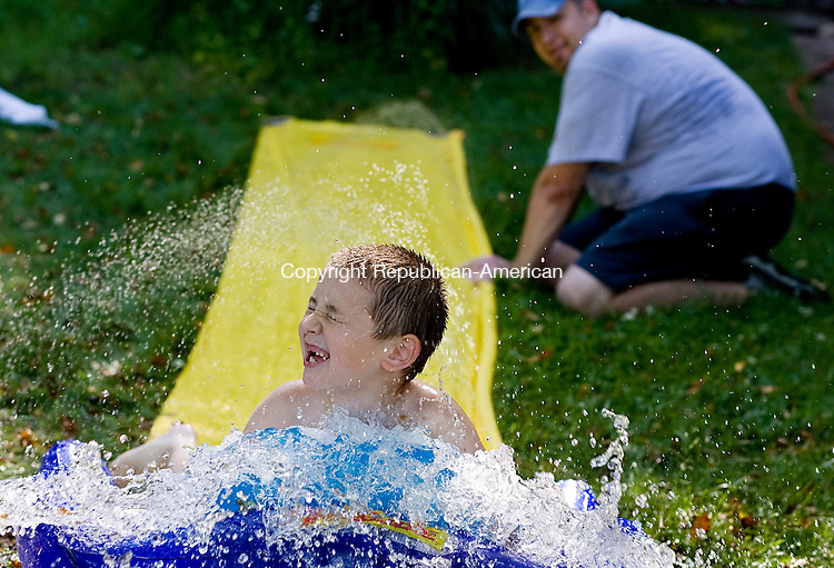 THOMASTON--09 June 08--060908TJ03 - Caleb Chaponis, 7, of Thomaston, plays on a slip 'n slide that his father, Matt, at right, bought earlier in the day after local schools let children out early due to the excessive heat on Monday, June 9, 2007. Visit www.rep-am.com to see other ways people beat the heat today. (T.J. Kirkpatrick/Republican-American)
