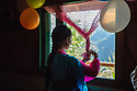 India - Sikkim - A Lepcha girl opens the curtains of her house located in a remote village lost ino the jungle.