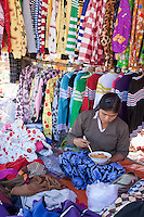 "Myanmar, Burma.  Clothing Vendor Eating Noodles with Chopsticks, ""Five-Day"" Market, Inle Lake, Shan State."
