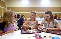 NWA Democrat-Gazette/BEN GOFF @NWABENGOFF<br /> Jean Visnich, a member of the Bella Vista Woodcarvers Club, shows Elizabeth Cook (left) and sister Sarah Cook of Harrison how to carve using butter knives and bars of soap Saturday, July 15, 2017, during the Bella Vista Woodcarvers Club's Artistry in Wood Show at Bella Vista Assembly of God church. Members of the club exhibited and sold their woodwork at the show, which also included door prizes, demonstrations and a people's choice award.