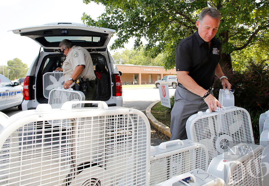 NWA Media/DAVID GOTTSCHALK - 6/30/14 - Tim Helder, right, Washinton County Sheriff, load electric fans into a sheriff vehicle with the help of Sgt. Oscar Henson, left, Monday June 30, 2014 at the Salvation Army of Northwest Arkansas Activity Center in Fayetteville. Monday marked the beginning of the Summer Fan Program. The Salvation Army will distribute fans through the Washington County Sheriffs Office, the city of Fayetteville Police and Fire Departments and Central EMS as well through their Social Service Office at the center to those in the community in need.