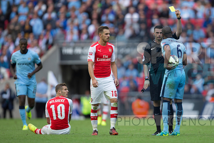 Referee Michael Oliver shows Fernando of Manchester City a yellow card for a challenge on Arsenal's Jack Wilshere - Arsenal vs. Manchester City - The FA Community Shield - Wembley Stadium - London - 10/08/2014 Pic Philip Oldham/Sportimage