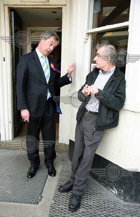 UKIP candidate Nigel Farage smokes a cigarette with locals outside the George pub in Winslow, Buckinghamshire, during the general election campaign.