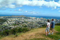 Couple at a park on O'ahu's Mount Tantalus look out at Honolulu, Diamond Head, Waikiki and the ocean.
