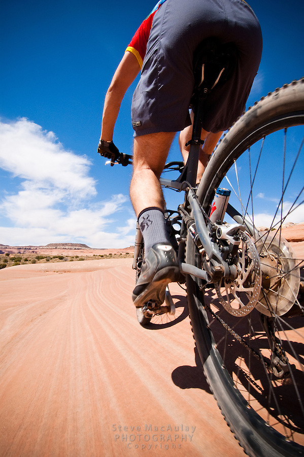 Male mountain biker on the striated slickrock dunes of Bartlet Wash, Moab, Utah