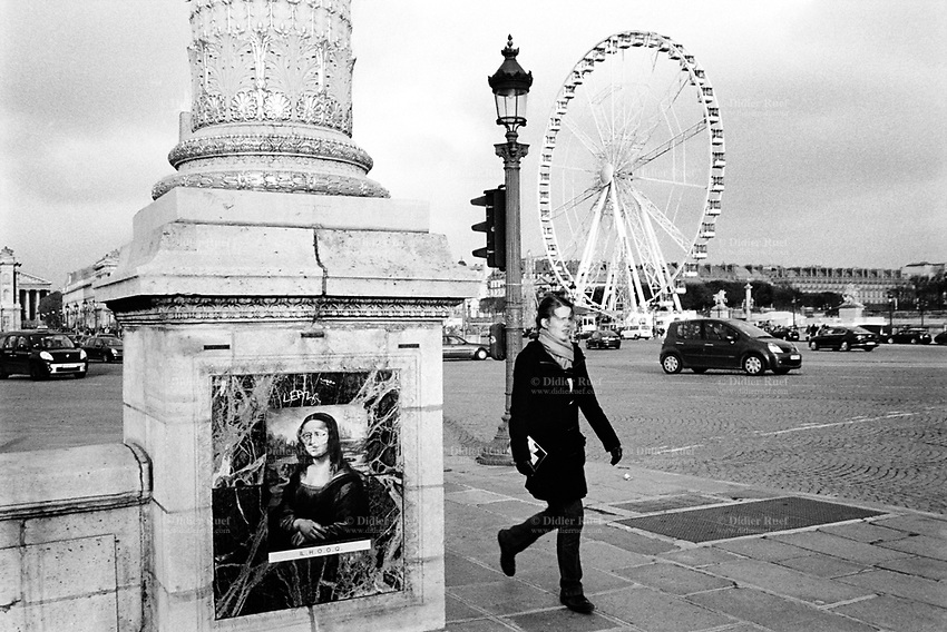 France. Ile-de-France Department. Paris. Concorde place. Traffic, pedestrians, big wheel and a poster with a drawing of Mona Lisa. The Mona Lisa (Monna Lisa or La Gioconda in Italian; La Joconde in French) is a half-length portrait of a woman by the Italian artist Leonardo da Vinci, The painting, thought to be a portrait of Lisa Gherardini, the wife of Francesco del Giocondo, is in oil on a white Lombardy poplar panel, and is believed to have been painted between 1503 and 1506, although Leonardo may have continued working on it as late as 1517. It is now the property of the French Republic, on permanent display at The Louvre museum in Paris since 1797. The ambiguity of the subject's expression, which is frequently described as enigmatic, the monumentality of the composition, the subtle modeling of forms and the atmospheric illusionism were novel qualities that have contributed to the continuing fascination and study of the work. 20.11.13 © 2013 Didier Ruef