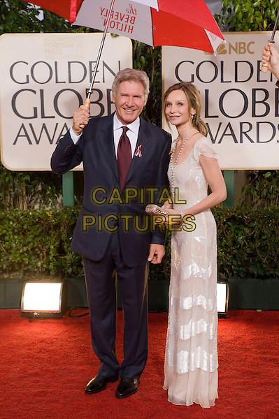 HARRISON FORD & CALISTA FLOCKHART.Arrivals at the 67th Golden Globe Awards held Beverly Hilton, Beverly Hills, California, USA..January 17th, 2010.globes full length couple white dress blue suit tie red sheer striped clutch bag beads necklace maxi umbrella .CAP/AW/HFPA.Supplied by Anita Weber/Capital Pictures