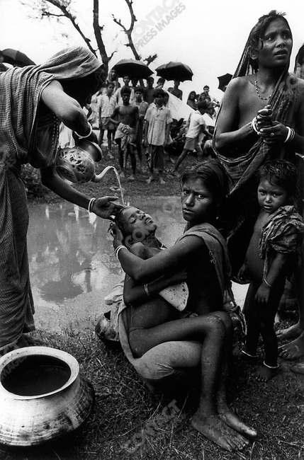 Bengali woman pours polluted water to cool a feverish child sick with cholera, border of India and Bangladesh, 1971