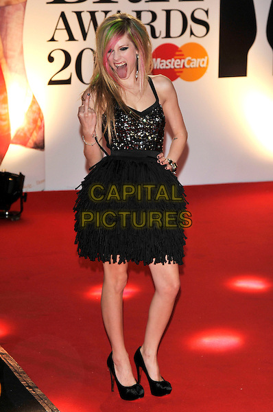 AVRIL LAVIGNE .The BRIT Awards 2011 - Arrivals at the O2 Arena, London, England, UK, .February 15th, 2011..brits full length black silver dress hand on hip green pink dyed hair streaks beaded tiered ruffles tassels mouth open funny finger swearing gesture hand .CAP/PL.©Phil Loftus/Capital Pictures.