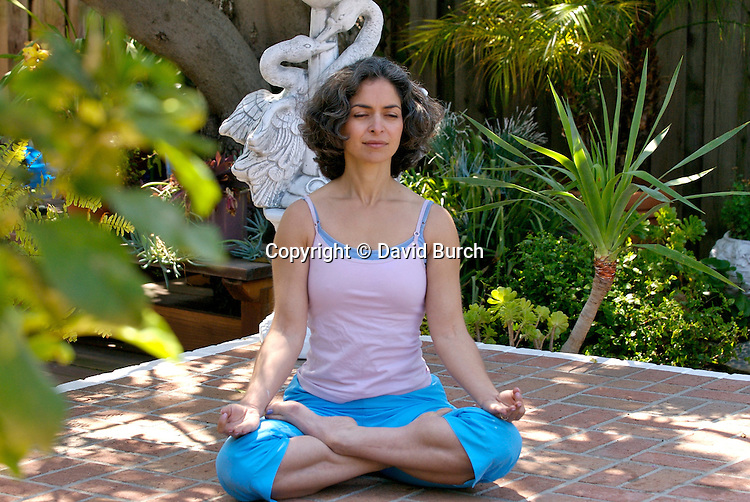 Mature woman meditating in garden with eyes closed