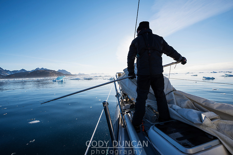Sailor with ice pole while navigating icy water near Tasiilaq, east Greenland