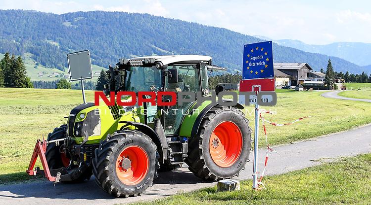 18.05.2020, Grenzübergang, Sulzberg (Vorarlberg), AUT, Coronavirus, Erleichterungen an der Grenze von Bayern nach Vorarlberg und Tirol, seit 13.05.2020 können Land- und Forstwirte von 7-20 Uhr weitere Grenzübergänge nutzen. Ein Landwirt bewirtschaftet eine Wiese. Ein Teil der Wiese befindet sich in Bayern, der andere Teil in Vorarlberg.<br /> im Bild ein Traktor passiert die Grenze<br /> <br /> Foto © nordphoto / Hafner