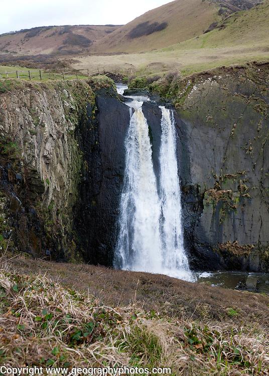 Speke's Mill Mouth waterfall as water  cascades over steep cliff, near Hartland Quay, north Devon, England