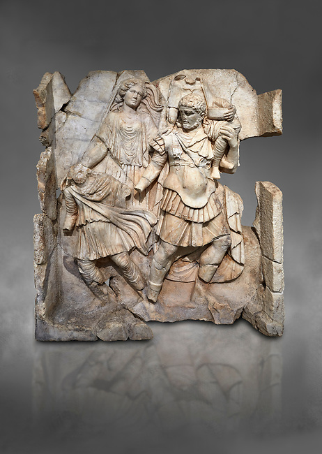 Roman Sebasteion relief  sculpture of Aineas' flight from Troy, Aphrodisias Museum, Aphrodisias, Turkey.  Against a grey background.<br /> <br /> Aineas in armour carries his aged farther Anchises on his shoulders and leads his young son Lulus by his hand. They are fleeing from the sack of Troy. The figure floating behind is Aphrodite, Aineas' mother: she is helping their escape. Old Anchises carries a round box that held images of Troy's ancestral gods.