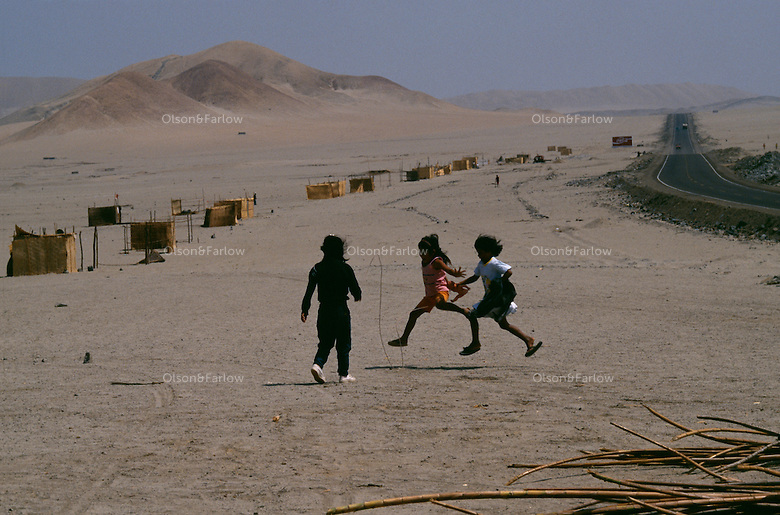 "Children jump rope and play beside the Pan American highway near the crumbling ancient fortress of Chanquillo.  A city is being erected by El Nino victims building houses out of cane or cana brava, optimistically calling their new home Mino de Oro or Gold Mine ""because of the possibilities.""  Many of the 2,000 displaced families stay with relatives while a non-profit organization helps them with the relocation.  The land is barren.  They are miles from water, but it is promised."