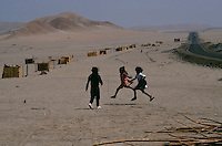 """Children jump rope and play beside the Pan American highway near the crumbling ancient fortress of Chanquillo.  A city is being erected by El Nino victims building houses out of cane or cana brava, optimistically calling their new home Mino de Oro or Gold Mine """"because of the possibilities.""""  Many of the 2,000 displaced families stay with relatives while a non-profit organization helps them with the relocation.  The land is barren.  They are miles from water, but it is promised."""