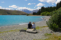 New Zealand, South Island, Canterbury region: Couple sitting beside Lake Tekapo | Neuseeland, Suedinsel, Region Canterbury: Paar am Ufer des Lake Tekapo