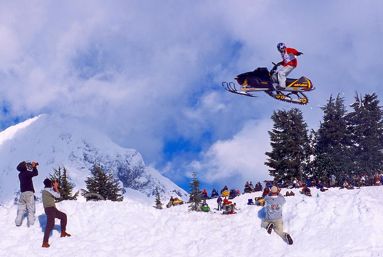 Man on Snowmobile jumping in Air at Competition Meet near Brohm Ridge, Garibaldi Provincial Park, Coast Mountains near Squamish, BC, British Columbia, Canada