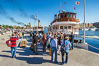 Människor på kajen vid Balsieholmen i Stockholm med ångbåtar på skärgårdsbåtens dag.