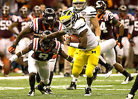 Michigan quarterback Denard Robinson runs the ball away from Virginia Tech defenders during Sugar Bowl game at Mercedes-Benz SuperDome in New Orleans, Louisiana on January 3rd, 2012.    Michigan defeated Virginia Tech, 23-20 in first overtime.