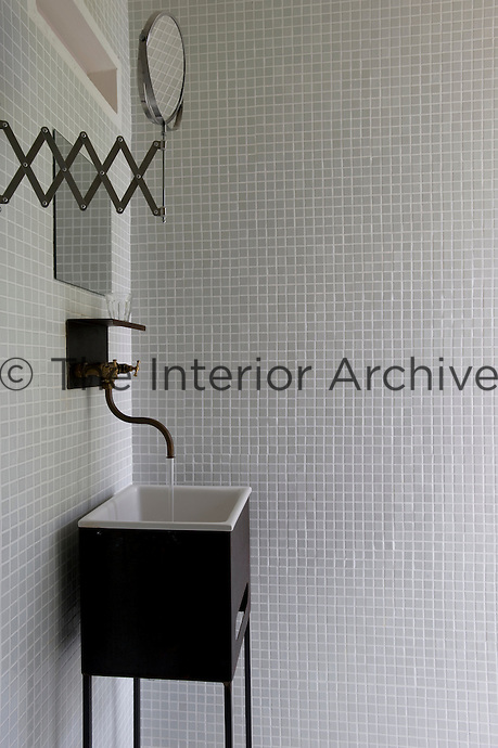 A contemporary washbasin on a stand in a bathroom that has been decorated with grey mosaic tiles