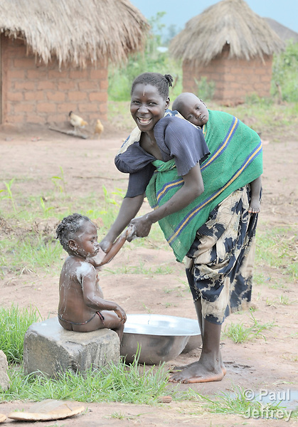 A woman bathes her child while another child rests on her back.