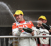 Race Two winner Jamie Whincup and second-placed Steven Johnson (right) spray champagne on the podium during Day Three of the Hamilton 400 Aussie V8 Supercars Round Two at Frankton, Hamilton, New Zealand on Sunday, 19 April 2009. Photo: Dave Lintott / lintottphoto.co.nz