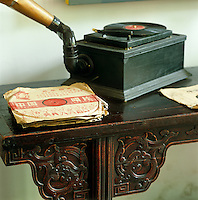An old-fashioned record player with a collection of vinyl records in Chinese sleeves