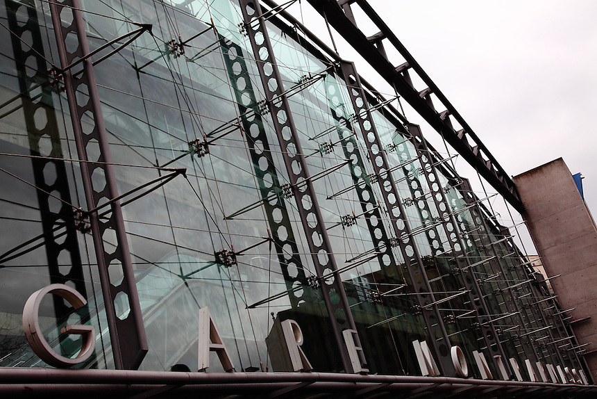 An artistic view of the front of the gare Montparnasse in Paris, with some inner details, such as the stairways, just distinguishable across the reflecting  glass walls,  on which part of the metal outer structure beautifully reflects itself, and, on the bottom, the well known name of the railway station. There are nice blue-green glares. Digitally Improved Photo.