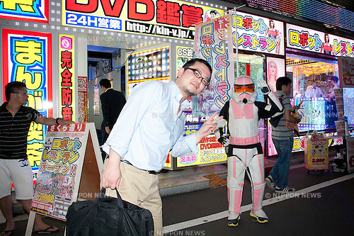 "July 23 2012, Tokyo, Japan - A Japanese costumer and a soldier of the Star Wars movie announces the ""Robot Restaurant"" at Kabukicho in Shinjuku. The restaurant advertises that cost 10 billion yen (130 million) opening. Robots run by real women dressed in military, perform cabaret dance for its customers, opened in the Kabukicho area, Shinjuku in Tokyo. (Photo by Rodrigo Reyes Marin/AFLO)"