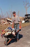 Man age 22 cleaning up after devastating tornado.  St Peter  Minnesota USA
