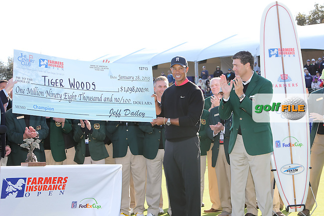 28 JAN 13  Tournament Champion Tiger Woods accepts the winners check at the conclusion of Sunday's Final Round of The Farmers Insurance Open at Torrey Pines Golf Course in La Jolla, California. (photo:  kenneth e.dennis / kendennisphoto.com)