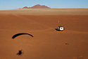 Namibia, Namib Desert, Namibrand Nature Reserve, shadow of powered paraglider on red sand, aerial view