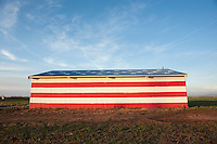 Outside of Fresno, CA a barn is painted to mirror the flag of the United States of America in a show of patriotic spirit.
