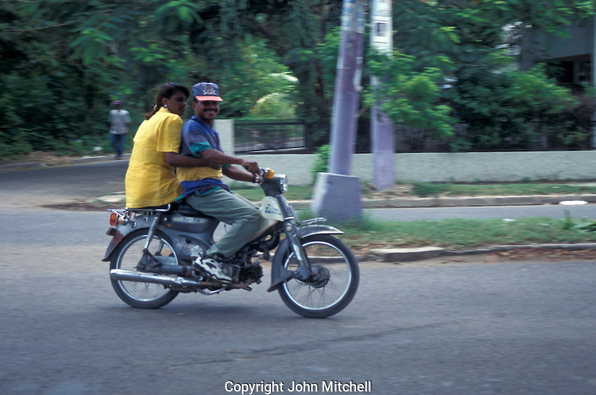 Man and a woman riding a small motorcycle in the city of Barahona, Dominican Republic