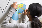Education Grade 6 female student at work geography social studies transferring map to wall horizontal