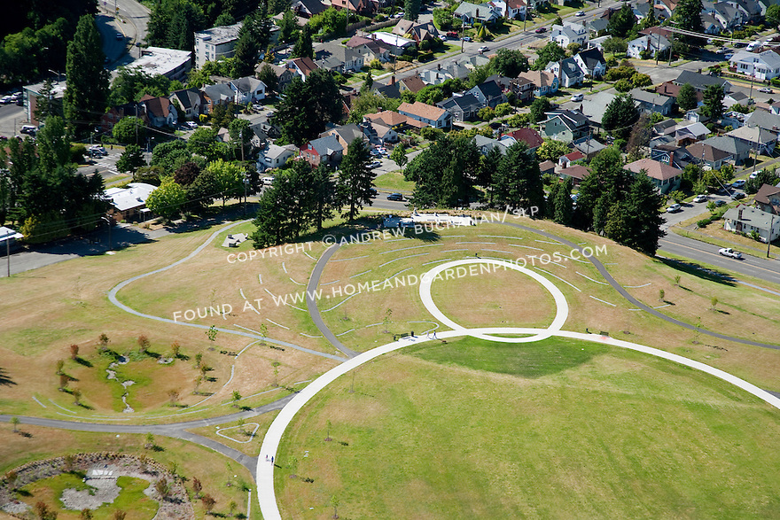 aerial photo of landscape art installation as part of the makeover of Seattle's Jefferson Park, former site of two urban reservoirs on Seattle's Beacon Hill; while the larger was buried underground and lidded, this smaller of the two is now drained and topped with playfields and these cement contour lines that show heights above sea level and represent the approximate shape of the former reservoir at various levels; Seattle, WA; July, 2011