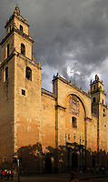 Oblique low angle view of the Catedral de San Ildefonso, 1561-98, Merida, Yucatan, Mexico, pictured on July 15, 2006, in the evening beneath a stormy sky. The twin-towered cathedral stands on the site of a Mayan temple, many of whose stones were incorporated in the building which was built by the Mayan workers. In 1542 Spanish Conquistadors, led by Francisco de Montejo (the Younger), captured the ancient Mayan city of Th'o, whose lime-mortared stone buildings reminded them of Roman architecture in Merida, Spain. Having demolished Th'o and built a new city, incorporating old Mayan materials in the cathedral and other impressive 16th century buildings, they named it after Merida. Merida is the state capital of Yucatan. Picture by Manuel Cohen.