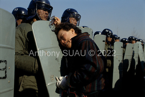 "Kuro gu, South Korea.December 18, 1987..A mother is separated from her arrested son by a wall of government police after a battle with students at a nearby polling station. The students claim that the polling station had been the filled with fraudulent votes....After two decades of building an economic miracle, in the summer of 1987 tens of thousands of frustrated South Korean students took to the streets demanding democratic reform. ""People Power"" Korean-style saw Koreans from all social spectrums join in the protests...With the Olympics to be held in South Korea in 1988, President Chun Doo Hwan decided on no political reforms and to choose the ruling party chairman, Roh Tae Woo, as his heir. The protests multiplied and after 3 weeks Chun conceded releasing oppositionist Kim Dae Jung from his 55th house arrest and shaking hands with opposition leader Kim Young Sam. Days later he endorsed presidential elections and an amnesty for nearly 3,000 political prisoners. It marked the first genuine initiative of democratic reform in South Korea and the people had their victory."