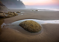 Hug Point State Park, Oregon: Colorful dawn sky and layer of ground fog at low tide