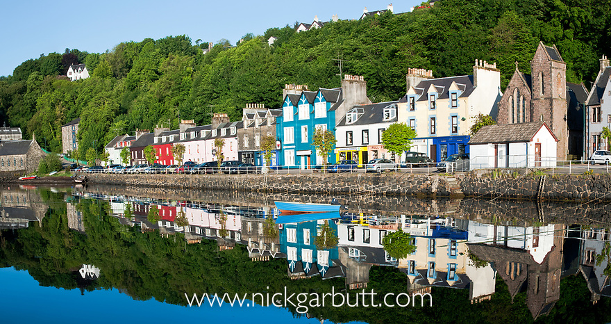Reflection of house and boat in the harbour in Tobermory, Isle of Mull, Inner Hebrides, Scotland, UK. June 2010.