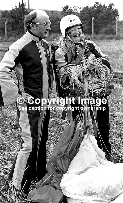 Mary Peters, N Ireland, Olympic Gold Medallist, women's pentathlon, back on terra firma following her first ever parachute jump from 2000 ft over Newtownards Airport, Co Down, N Ireland. 26h November 1974. With her in the photo is Colin Wallace, Ministry of Defence employee at British Army HQ, Thiepval Barracks, Lisburn.197411260667a<br /> <br /> Copyright Image from Victor Patterson, 54 Dorchester Park, Belfast, UK, BT9 6RJ<br /> <br /> t: +44 28 90661296<br /> m: +44 7802 353836<br /> vm: +44 20 88167153<br /> e1: victorpatterson@me.com<br /> e2: victorpatterson@gmail.com<br /> <br /> For my Terms and Conditions of Use go to www.victorpatterson.com