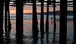 Santa Monica beach is seen through pylons underneath the Santa Monica Pier