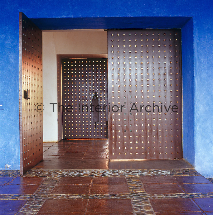 A sequence of large, iron-plated double doors peppered with inlaid glass creates a grand entrance hall yet with a minimalist touch