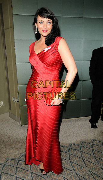 MARTINE McCUTCHEON .Attending the Pink Ribbon Ball at the Dorchester Hotel, Park Lane, London, England, UK, October 10th 2009..full length  red long maxi dress pleated tiered clutch bag ruffles ruffle .CAP/CAN.©Can Nguyen/Capital Pictures.