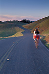 Cyclist biking on bicycle along twisting mountain road, Bolinas Ridge, Mount Tamalpais State Park, Marin, California