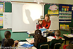 Education Elementary school Grade 2 female teacher and female student using overhead transparency projector to do mathematics addition problem horizontal