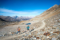 Two women trail running in a wide open rocky landscape on Piz Languard, above Pontresina, Switzerland