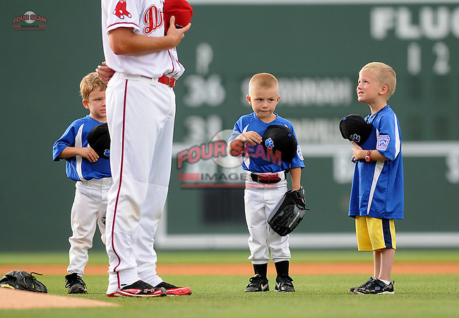 Three youth baseball players stand with pitcher Madison Younginer during the National Anthem before a game between the Savannah Sand Gnats and the Greenville Drive on May 29, 2012, at Fluor Field at the West End in Greenville, South Carolina. (Tom Priddy/Four Seam Images)