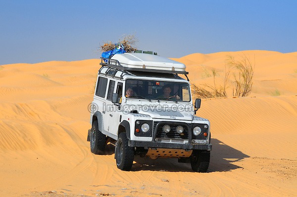 Africa, Tunisia, nr. Tembaine. Land Rover Defender 110 TD5 Station Wagon on its way through a stretch of sand dunes close to Tembaine on the eastern edge of the Grand Erg Oriental. --- No releases available, but releases may not be needed for certain uses. Automotive trademarks are the property of the trademark holder, authorization may be needed for some uses.